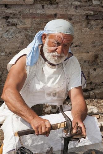 Bu adamın orada rolü ne onu çıkaramadık ama kaptırmış ustalıkla işini yapıyor. Belki de gladyatörlerin kopan sandaletlerini tamir ediyor...