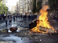 Kurdish protesters set fire to a barricade set up to block the street as they clash with riot police in Diyarbakir