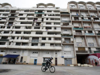 A boy rides his bike past a council housing block in the Les Moulins neighbourhood in Nice