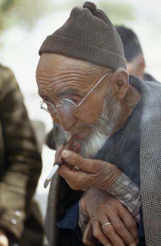 An elderly Turkish farmer smokes a cigarette.